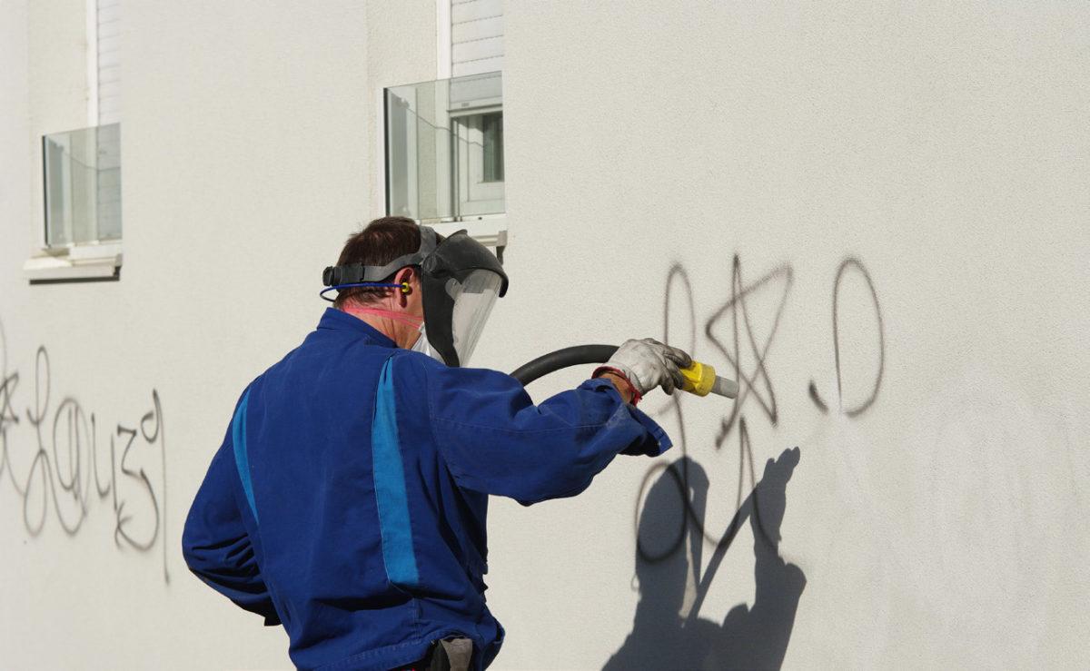 Mann entfernt Graffiti von Hauswand.