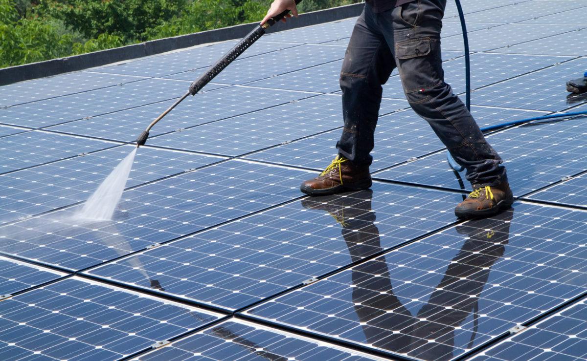 Mann säubert Solarflächen.
